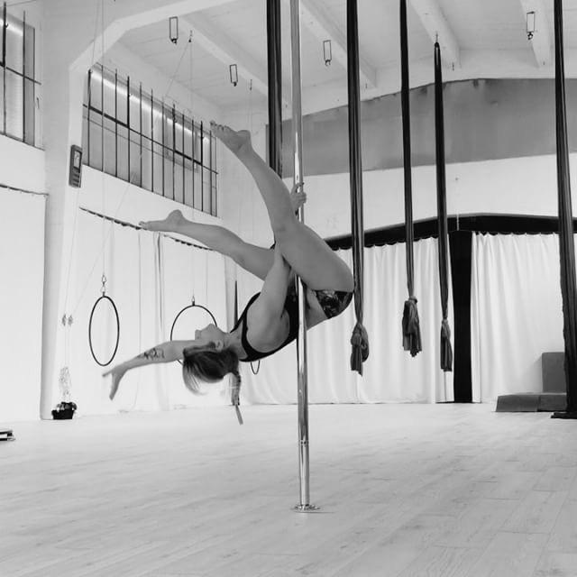 Jenny an der Pole Dance Stange. Einhändiger Invert.